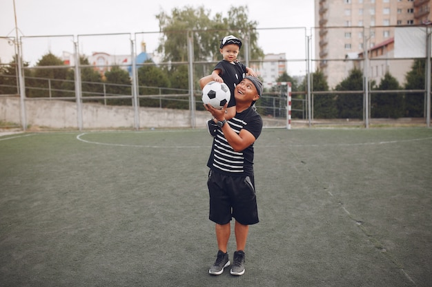 Отец с маленьким сыном играют в футбол
