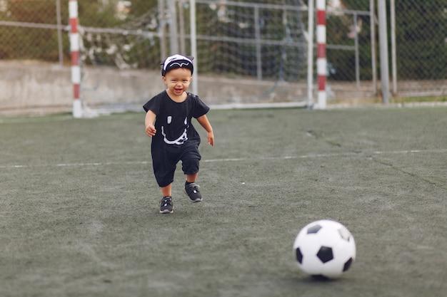 スポーツグラウンドでサッカーをしている少年