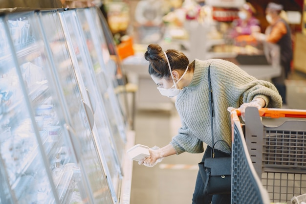 スーパーマーケットで防護マスクの女性