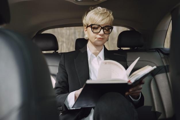 Коммерсантка сидя внутри автомобиля и использует тетрадь