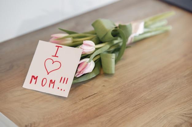 木製のテーブルの母の挨拶母と花の花束