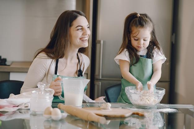 母と娘はクッキーのために生地を調理します