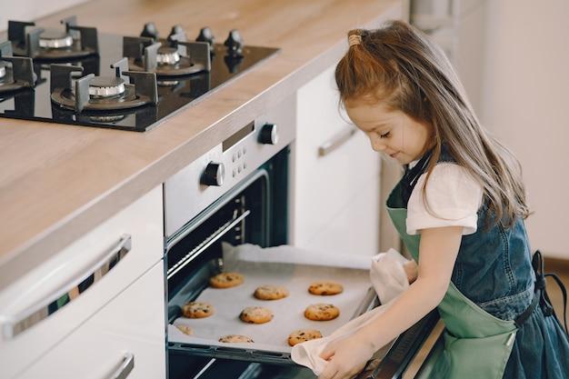 小さな女の子がオーブンからクッキートレイを引っ張る