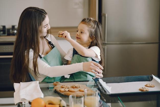 母と娘のクッキーが付いている台所に座っています。
