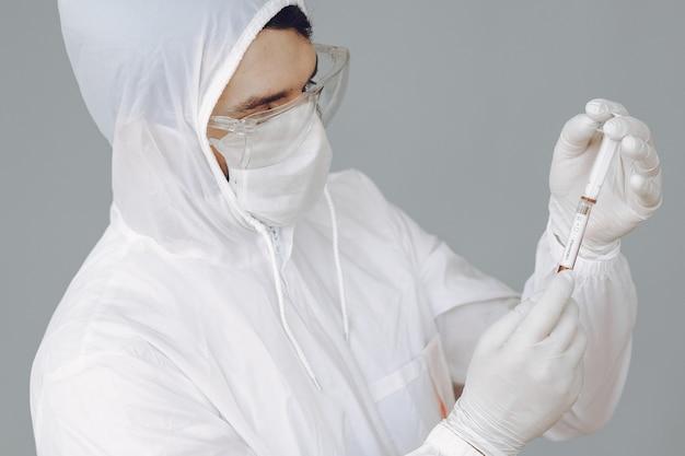防護服と実験室で働くメガネの男