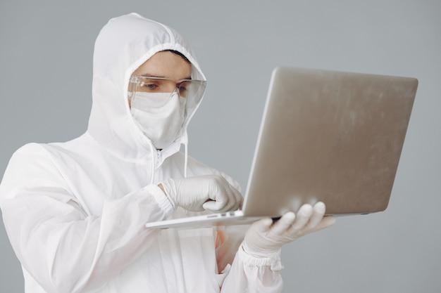 Человек в защитном костюме и очках, работающих в лаборатории