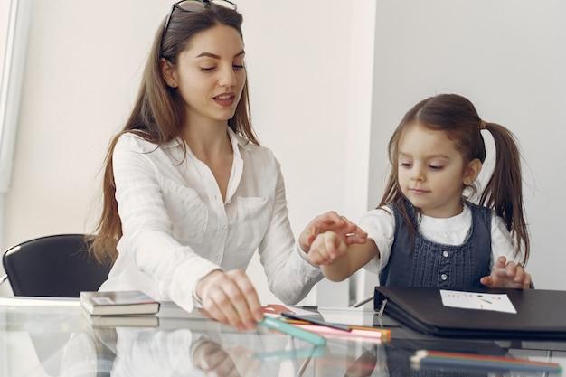 Репетитор с маленькой девочкой, занимающейся дома