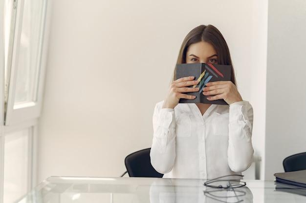 ノートが付いているオフィスに立っている女の子