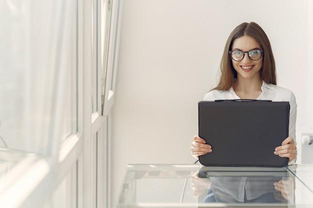 Девушка стояла в офисе с ноутбуком