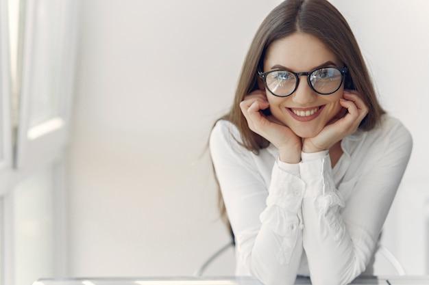 Деловая женщина в белой рубашке сидит в офисе