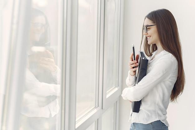 Девушка стояла в офисе с папкой