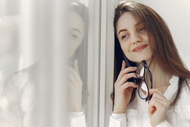Девушка стояла в офисе с телефоном
