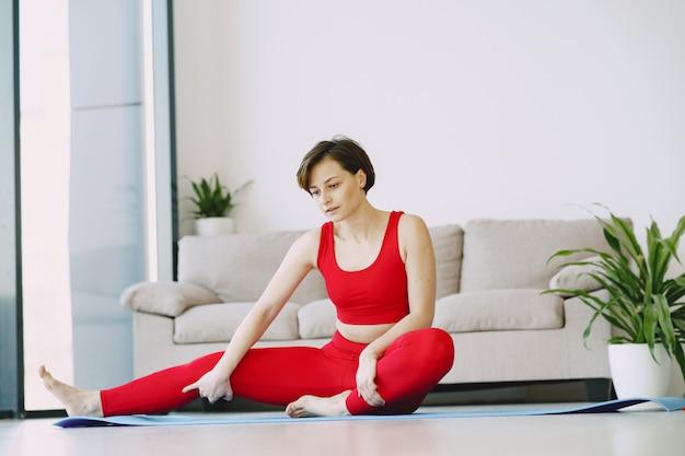 Девушка в красной спортивной форме практикующих йогу дома