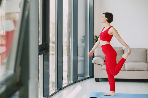 自宅でヨガの練習赤いスポーツ服の女の子
