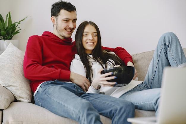 ソファーで映画を見て美しいカップル