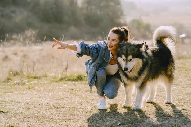 犬と日当たりの良いフィールドでスタイリッシュな女の子