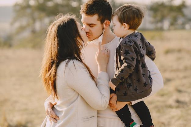 Стильная семья в масках гуляет по солнечному полю
