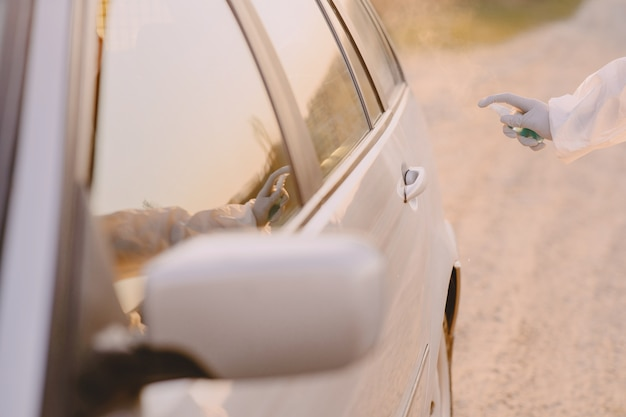 Человек в защитном костюме дезинфицирует машину