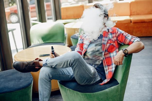 Стильный и элегантный мужчина сидит в кафе с вейпом