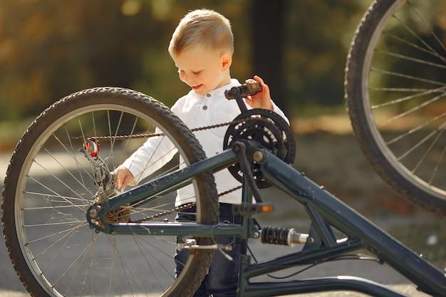 Маленький мальчик ремонтировать свой велосипед в парке