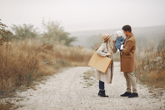 秋のフィールドを歩いてスタイリッシュな家族
