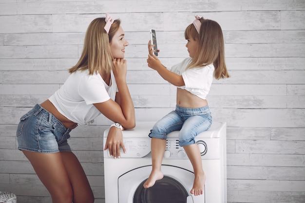 洗濯機の近くのバスルームで母と娘