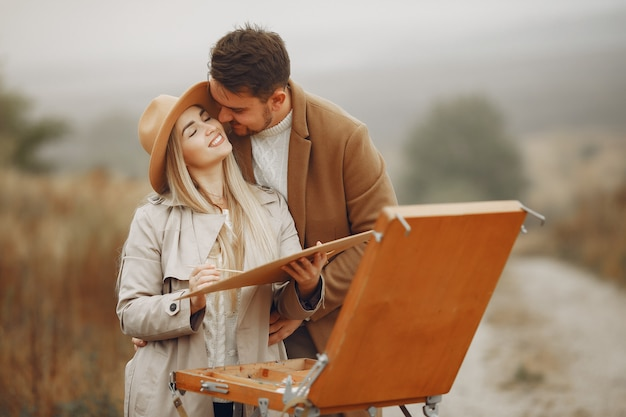 秋のフィールドでエレガントなカップルの絵画