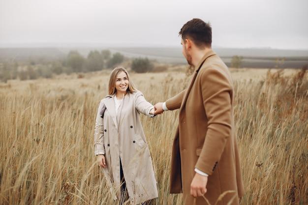 美しいカップルは秋のフィールドで時間を過ごす
