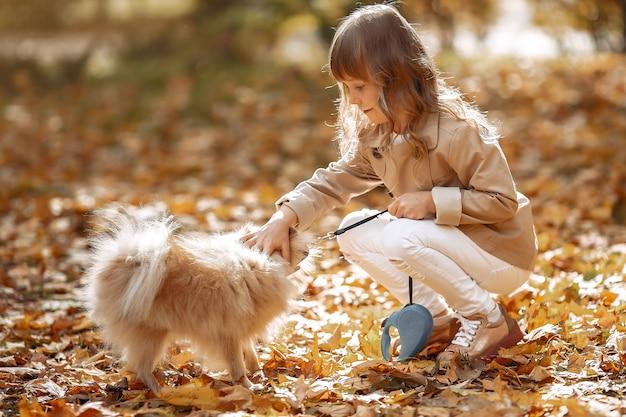 かわいい女の子が犬と一緒に秋の公園で散歩します。