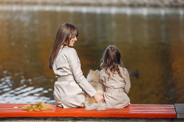 川の近くに座っている娘を持つ母