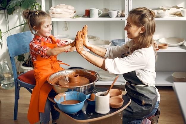 陶器の機械で粘土から渦を巻く人々