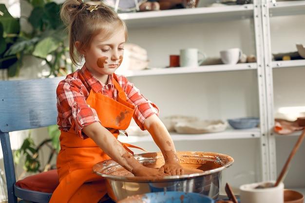 陶器の機械で粘土から迷路を作る女の子