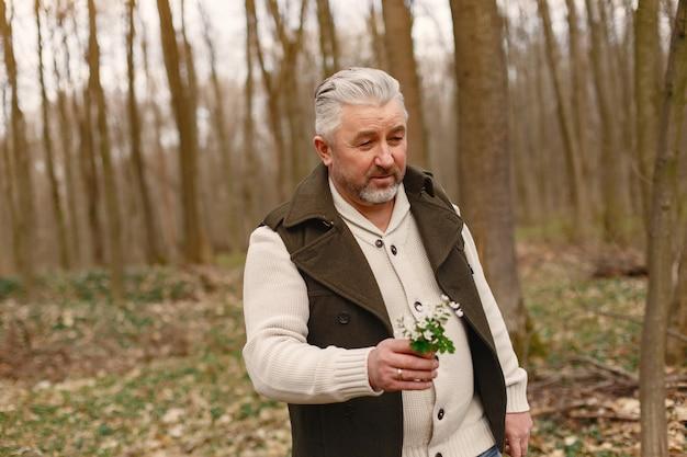 Элегантный взрослый мужчина в весеннем лесу