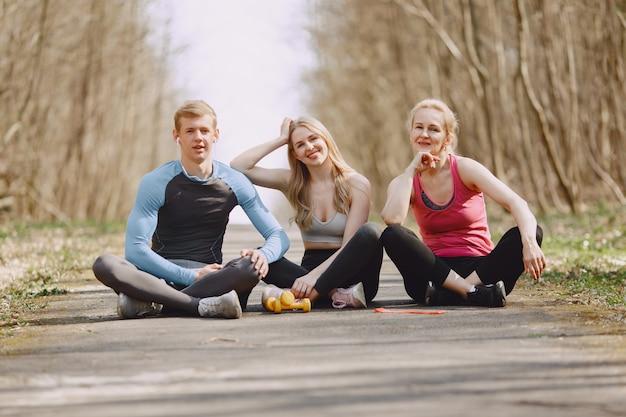 Спортивная семья сидит в летнем лесу