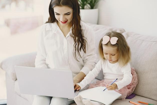 Женщина с дочерью, используя портативный компьютер