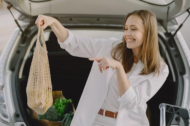 Женщина позирует с сумкой для покупок на своей машине