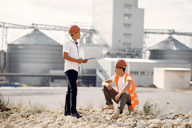 工場のそばに立っているヘルメットのエンジニア