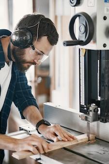 Профессиональный плотник работает с пильной машиной