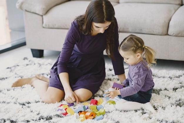 小さな子供の娘と一緒に笑って遊ぶ陽気なママ