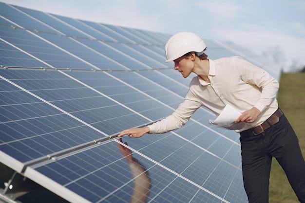 太陽電池の近くの白いヘルメットのビジネスマン