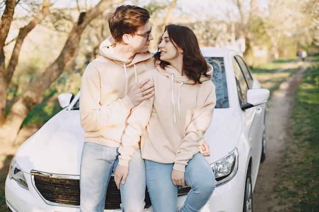 Пара сидит на капоте автомобиля в парке