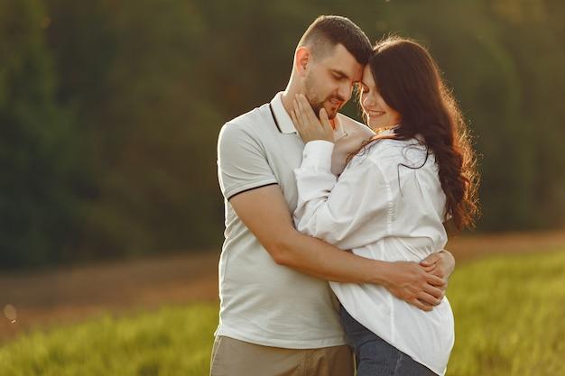 美しいカップルは夏の畑で時間を過ごす