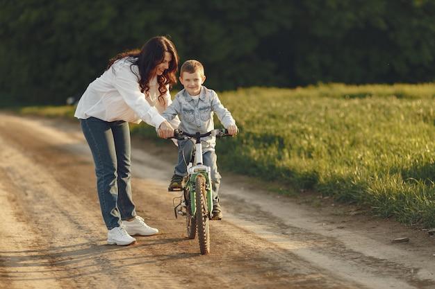 秋のフィールドで遊ぶ幼い息子を持つ母