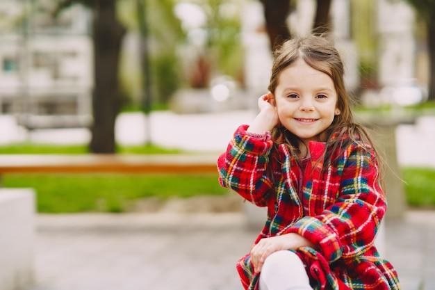 Маленькая девочка в парке сидит на скамейке