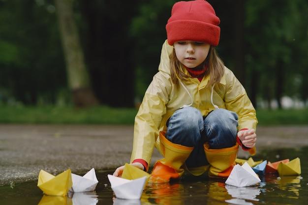 水たまりで紙の船で遊んで長靴で面白い子供たち