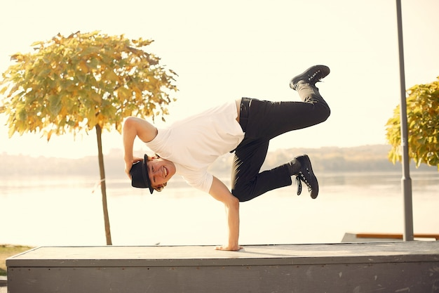Молодой случайный человек танцует открытый в городском парке