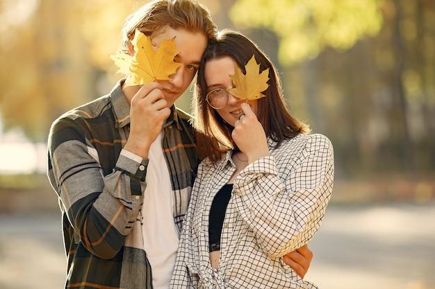 美しいカップルは秋の公園で時間を過ごす