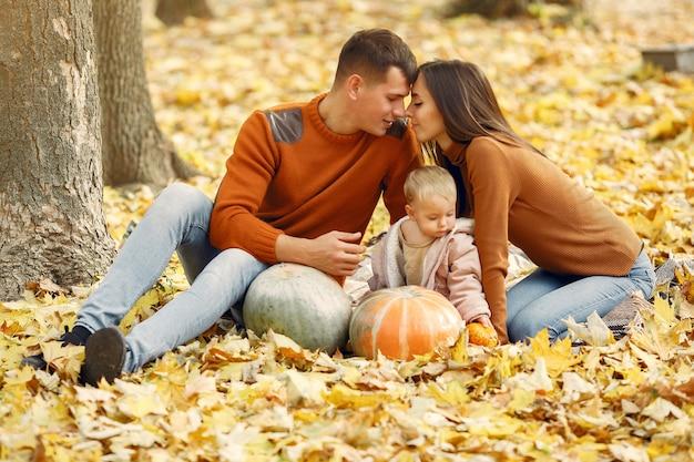 秋の公園で小さな娘と家族