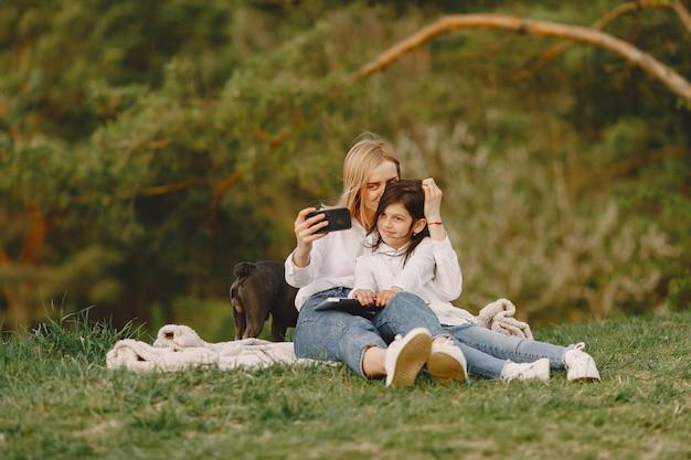 Элегантная мама с дочерью в летнем лесу