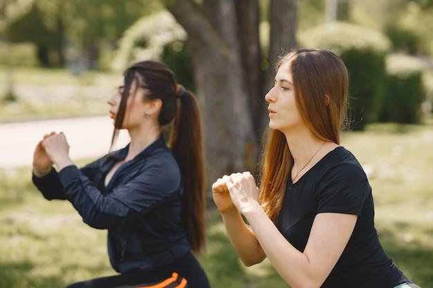 Милые девушки занимаются йогой в парке летом